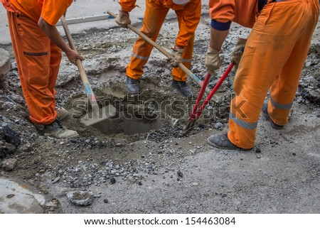 workers work on the replacement of cover slab with cast iron cover on the road with the help of a shovel and Bolt Cutter - stock photo