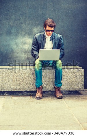 Working anywhere. Wearing black leather jacket, blue jeans, brown boot shoes, sunglasses, a young guy with beard sitting on marble bench against wall on street, working on laptop computer.  - stock photo