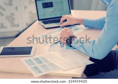 Working at a computer. Close-up view of the hands of the laptop while two successful businessman sitting at the table against each in the business office in formal wear and work at a laptop. - stock photo
