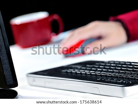 Working at Home A lady in red blouse is using her wireless mouse at a computer workstation. She is working at home. Shallow D.O.F - stock photo