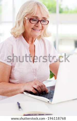 Working at home. Happy senior woman working at the laptop and smiling while sitting at the table