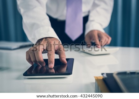 Working business man calculate on calculator and using computer tablet on modern desk in the workplace office, modern view hipster in vintage. - stock photo