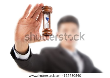 Working businessman hold a hourglass timer in hands - stock photo