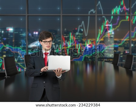 Working businessman in the office. Forex graph and an amazing night view of the business city area. A metaphor of international financial consulting.
