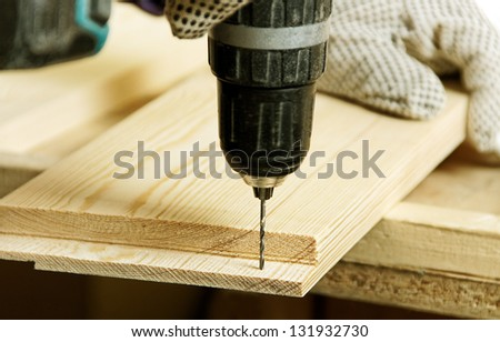 Working carpenter with drill. - stock photo