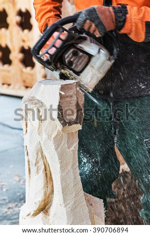 Working chainsaw carving figures from the log. Focus on a log