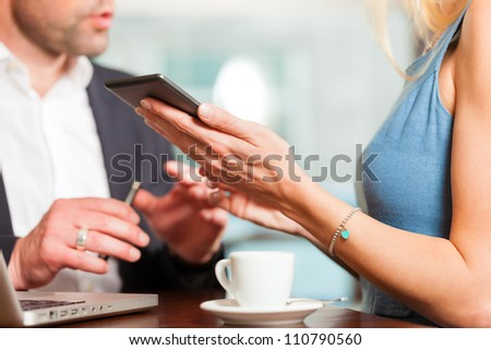 Working colleagues - a man and a woman - sitting in cafe working and drinking coffee - stock photo
