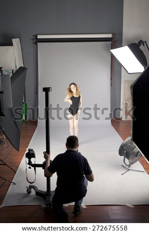 Working conditions in the studio, the photographer photographs the professional model - stock photo