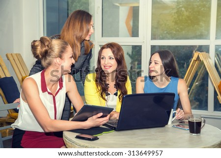 Working days in the women's team. Four young women - office staff. Discussion of joint work on the project. Female business. Women working in the office at the computer. Group of women. Toned image.