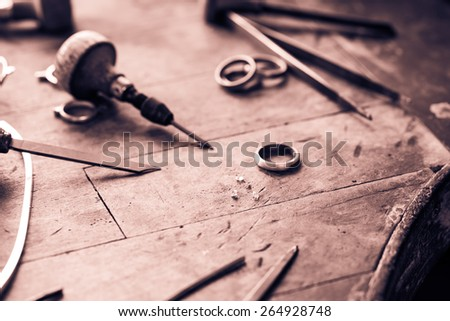 Working desk for craft jewelery making with professional tools. Grunge wooden table. Monochrome cream tone. Black and white photography. - stock photo