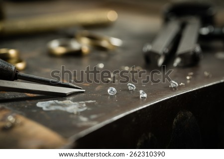 Working desk for craft jewelery making with professional tools. Still life of goldsmith's tools with diamonds. Macro shot. - stock photo