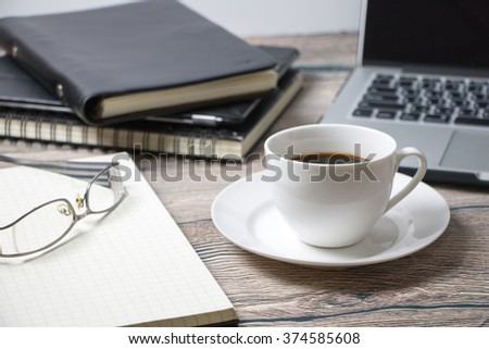 Working desk with coffee laptop glasses book notepad supplies and tablet  on wooden desk