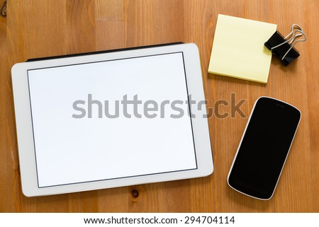Working desk with digital tablet showing a blank screen for advertising - stock photo