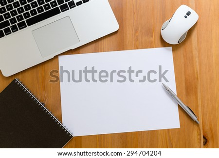 Working desk with laptop computer blank paper for advertising - stock photo