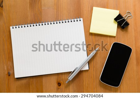 Working desk with mobile phone and empty handbook for adding some graph - stock photo