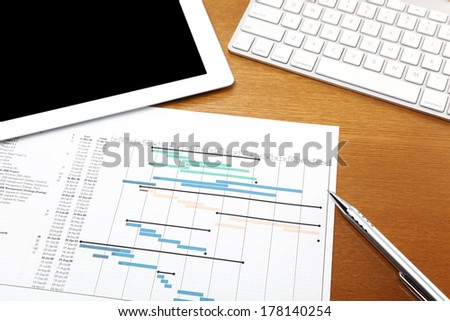 Working desk with project gantt chart - stock photo