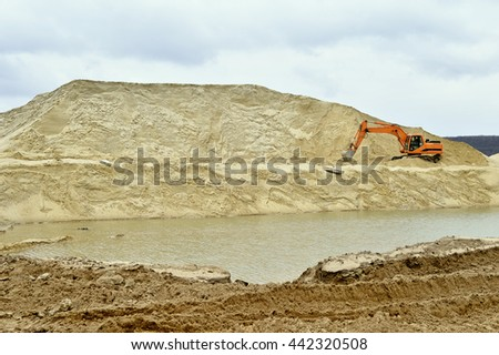 Working digger in a quarry produces sand.