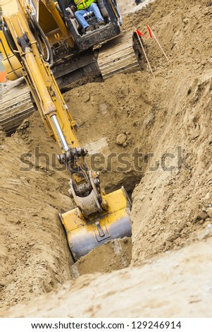 Working Excavator Tractor Digging A Trench. - stock photo
