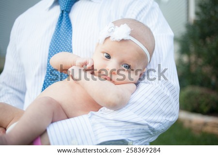 Working father holds two month old Baby girl - stock photo