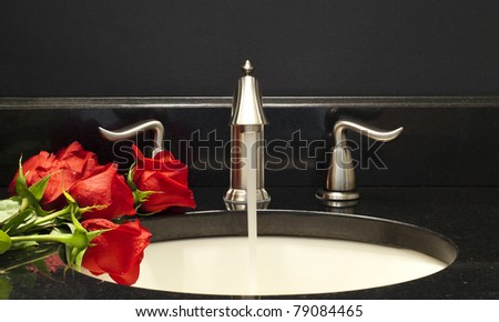 Working faucet  and a few red roses on a sink. - stock photo