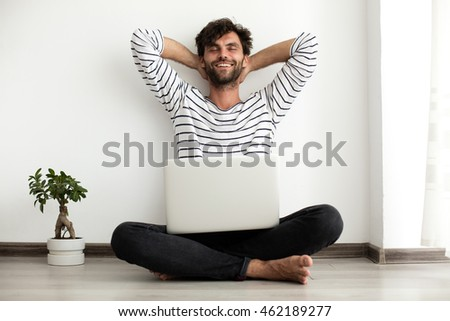 working from home concept with young relaxed man sitting down on the floor working at laptop with a plant next to him