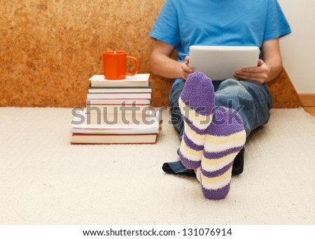 Working from home. Man relaxing in bed using digital tablet, close up on male foots in socks. - stock photo