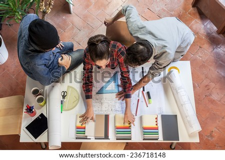 Working Group. Three young architects working on a project at a table in the study - stock photo