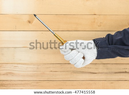 Working hand in glove holding screwdriver with wall wood background