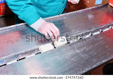 Working hand puts a bar of soap on the conveyor. - stock photo