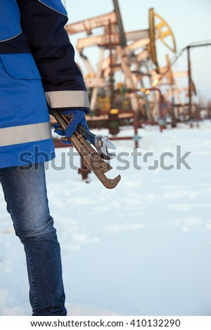 Working hand with wrenches on a wellhead crude oil site background. Petroleum concept. - stock photo
