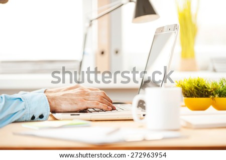 Working hard to meet deadlines. Close-up of young man working on laptop while sitting at his working place - stock photo
