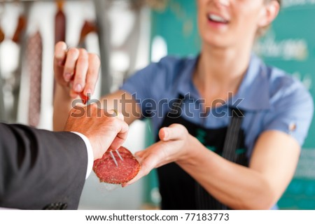 Working in a butcher's shop - shop assistant and client
