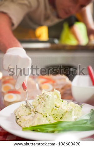 Working in a butchers shop - a shop assistant with curd cheese