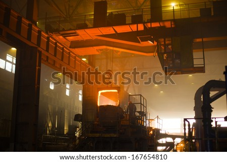 Working in a foundry, red color is a reflection of the molten metal. Very high heat and purple fringing. See more images and video from this series. - stock photo