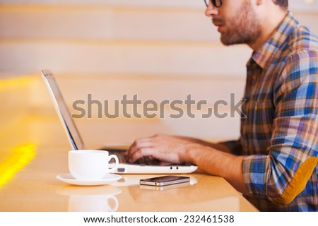 Working in coffee shop. Side view cropped image of thoughtful young man working on laptop while sitting in coffee shop - stock photo