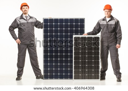 working in hard hat with solar panels in the studio job background - stock photo