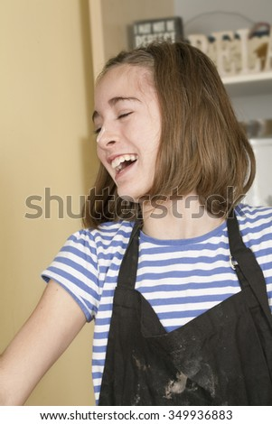 Working in the Kitchen. A young girl, taken as a head and shoulder portrait, during a baking session. She is laughing at a joke that had been made.