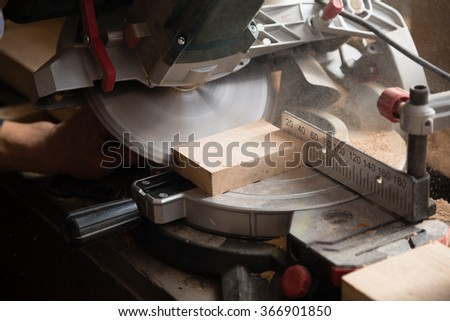 Working machine with a circulation saw in the carpentry workshop.