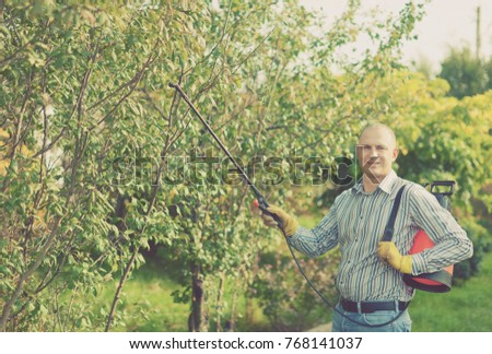 working man with garden spray  in orchard