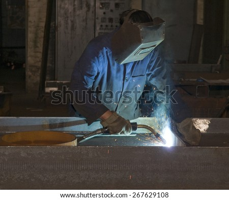 Working man with helmet shield on his head is welding  steel construction. Hard work in the production department. - stock photo