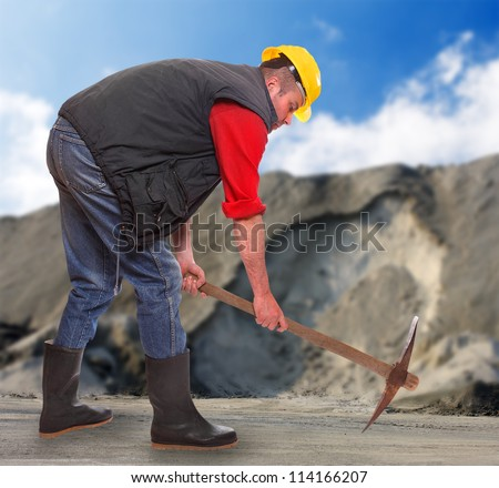 Working man with pick axe in a coal mine. Under construction concept.