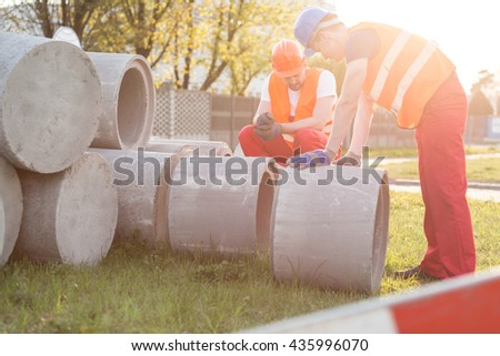 Working men with concrete rings on the construction site - stock photo