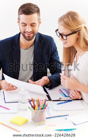 Working moments. Two confident business people in smart casual wear sitting together at the table and discussing something while looking at the document - stock photo