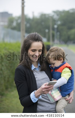 Working Mother holding baby and using mobile phone in street. - stock photo