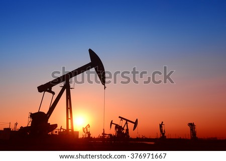 Working oil derrick in field under the setting sun