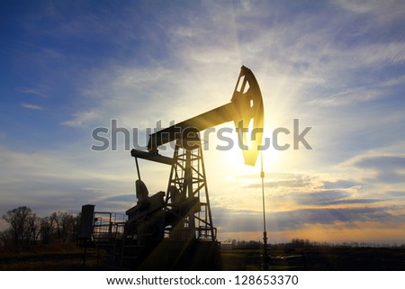 working oil pump at sunset with sunbeams - stock photo