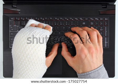 Working on a notebook with hand injury - stock photo