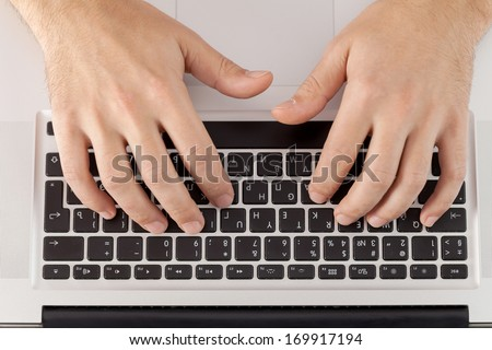 Working on computer. Top view of hands typing something on computer keyboard - stock photo