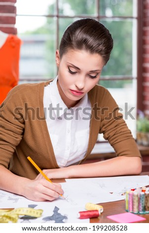 Working on creative fashion look. Beautiful young woman drawing fashion sketch while sitting at her working place