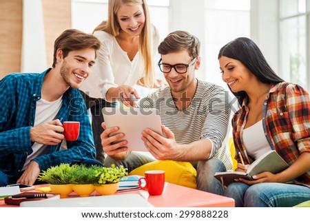 Working on creative project together. Group of happy young people looking at digital tablet while sitting on the colorful bean bags in office - stock photo